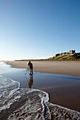 Photographer on the beach underneath Bamburgh Castle, Bamburgh, Northumberland, England, Great Britain, Europe