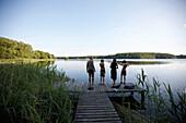 Family on jetty at lake Goldensee, Klein Thurow, Roggendorf, Mecklenburg-Western Pomerania, Germany