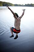 Boy juming into lake Goldensee, Klein Thurow, Roggendorf, Mecklenburg-Western Pomerania, Germany