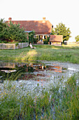 View over a pond to a house with garden in the evening, Klein Thurow, Roggendorf, Mecklenburg-Western Pomerania, Germany