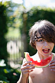 Boy eating a piece of watermelon, Klein Thurow, Roggendorf, Mecklenburg-Western Pomerania, Germany