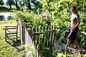 Woman with a watering can in a garden, Klein Thurow, Roggendorf, Mecklenburg-Western Pomerania, Germany