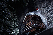 Young skier jumping down from a small wooden hut at darkness, Chandolin, Wallis, Switzerland, Europe