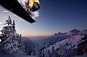 Snowboarder during a jump in front of panorama of mountains, Hahnenkamm, Tyrol, Austria, Europe