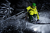 Young skier jumping through trees in the deep powder snow at darkness, Chandolin, Wallis, Switzerland, Europe