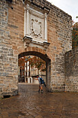 Pilgrim in front of Portal a Francia, town gate at the old town, Pamplona, Camino Frances, Way of St. James, Camino de Santiago, pilgrims way, UNESCO World Heritage, European Cultural Route, province of Navarra, Northern Spain, Spain, Europe
