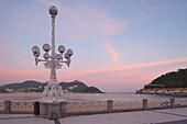 Street lamp at the seaside promenade at dusk, Playa de la Concha, Bahia de la Concha, San Sebastian, Donostia, Camino de la Costa, Camino del Norte, coastal route, Way of St. James, Camino de Santiago, pilgrims way, province of Guipuzcoa, Baskenland, Eusk