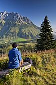 View from Hochkeil onto Mandlwand, hiker having a rest, Hochkoenig, Salzburg, Austria, Europe
