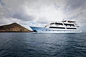 Luxury yacht under clouded sky off Bartolome Island, Galapagos, Ecuador, South America