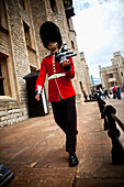 Coldstream Guard sentry patrolling the entrance to the Jewel House, Tower of London, London, England