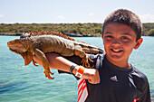 Boy with iguana, Ctenosaura similis, on arm at Xel-Ha Water Park, Tulum, Riviera Maya, Quintana Roo, Mexico
