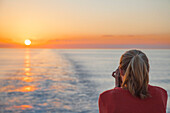 Young woman taking photographs of the sunset from cruise ship MS Deutschland (Reederei Peter Deilmann), Caribbean Sea, near Cayman Islands