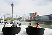 Cafe at the Media Harbour, television tower and buildings designed by Frank Gehry, Duesseldorf, North Rhine-Westphalia, Germany, Europe
