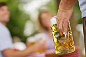 Hand holding a stein at a beer garden, Munich, Bavaria, Germany, Europe