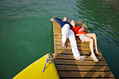Young couple lying relaxed on a jetty, Woerthsee, Bavaria, Germany, Europe