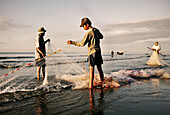Fishermen folding their nets on the beach after work, Mui Ne fishing village, Vietnam, South China Sea
