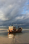 traditional wooden Fishing boat on the beach in the seaside resort of Ahlbeck in sunlight before thundershower, Usedom, Mecklenburg-Vorpommern, Germany, Europe
