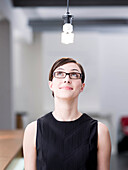 Woman looking at a light bulb