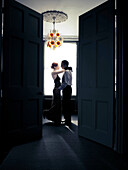 Young woman dancing with older man. Young woman dancing passionately with older man. Viewed through door opening.