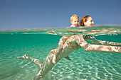 Mother giving toddler a piggyback ride. Woman swimming in crystal clear sea with young boy on her back, they are both smiling. Shot in profile from both above and below water. Underwater shot.