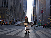 Elegant woman crossing New York street. Woman with shopping bags crossing New York street. Sky scrapers behind her. She is looking at camera, smiling.