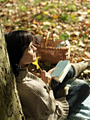 Woman reading under tree in Autumn