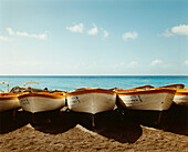 line of painted boats on beach. Wooden boats lined up on the beach at Positano, with sea behind