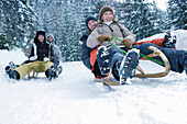 Teenagers riding sled in the snow. Group of young people with winter clothes having fun riding sled in snowy landscape.