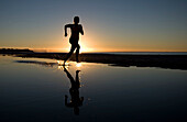 Young Woman Running on Beach at Sunset. Young Woman Running on Beach at Sunset