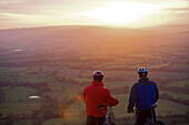 Two mountain bikers viewing scene. View of two mountain bikers standing together looking at a sunset.