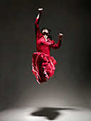 Woman in Red dress dancing under light