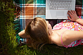 Woman lying on blanket using laptop. Young woman lying outdoors on picnic blanket using laptop computer