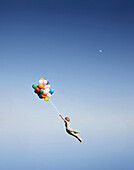 Woman floating away with balloons