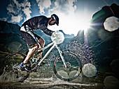 Male mountain biker riding through water