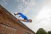 Athlete vaulting over brick wall. Athlete vaulting over brick wall
