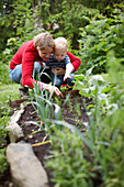 Mother and son examining plants. Mother and son examining plants