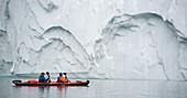 Men with cameras kayaking near glaciers. Men with cameras kayaking near glaciers