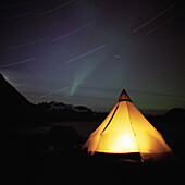 Camp tent lit from within at night. Camp tent lit from within at night