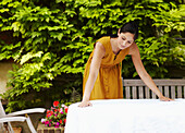 Woman spreading tablecloth outdoors. Woman spreading tablecloth outdoors