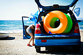 Woman unloading beach toys from car. Woman unloading beach toys from car