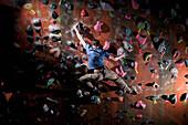 Man climbing indoor rock wall. Bouldering