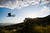 Mountain biker jumping on hillside. I_Street, dirt jumping, BMX