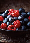 Bowl of blueberries and strawberries. Blueberries and Raspberries in wooden bowl