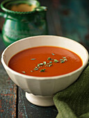 Close up of bowl of tomato soup. Tomatoe soup garnished with fresh thyme