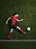 Soccer player laying on pitch. Soccer player kicking ball, lying on stadium grass