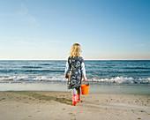 Girl walking in rainboots on beach