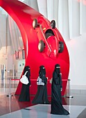 Three women in traditional black abayas at Ferrari World theme park in Abu Dhabi UAE United Arab Emirates