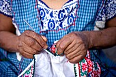 A woman stitches a design on the top of a blouse in Cuetzalan del Progreso, Mexico. Cuetzalan is a small picturesque market town nestled in the hills of Mexico´s central state of Puebla Founded in 1547 by Franciscan friars, this town took its name from th