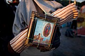 A pilgrim carries on his back an image of the Our Lady of Guadalupe in Mexico City, December 11, 2010  Hundreds of thousands of Mexican pilgrims converged on the Our Lady of Guadalupe Basilica, bringing images to be blessed, as processions filled the stre