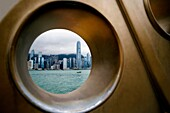 CHINA HONG KONG HONG KONG COASTLINE VICTORIA HARBOUR View of Hong Kong's coastal frontline skyline shoot through a hole, part of a bronze sculpture at Kowloon's side road called Avenue of Stars, shoot on a cloudy day